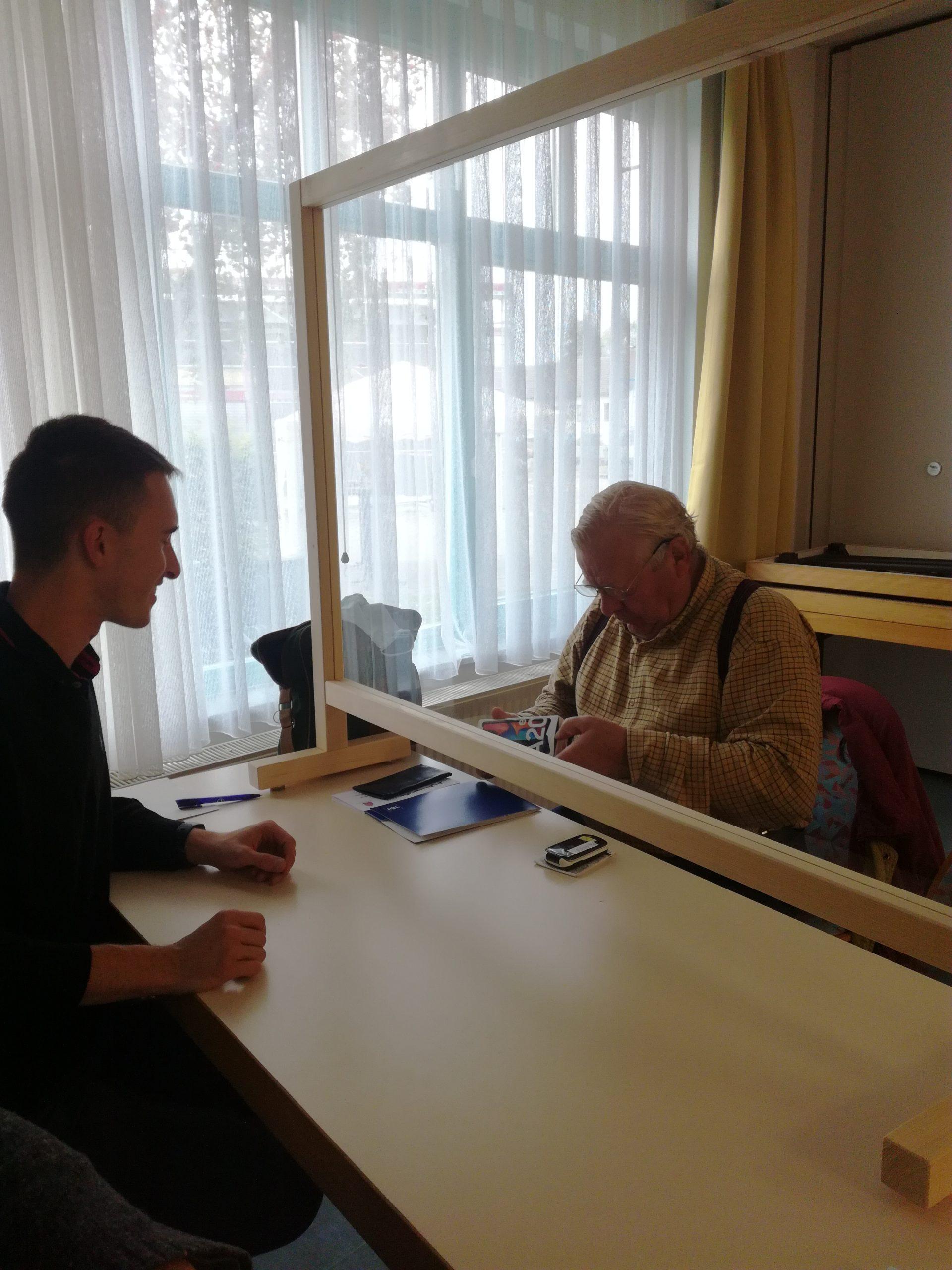 Auf dem Bild sind zwei Männder zu sehen. Der jüngere Mann sitzt links im Bild an einem Tisch. In der Mitte des Tisches befindet sich eine transparente Trennwand. Gegenüber von dem jüngeren Mann sitzt ein älterer Mann. Er blättert in einem Heft.